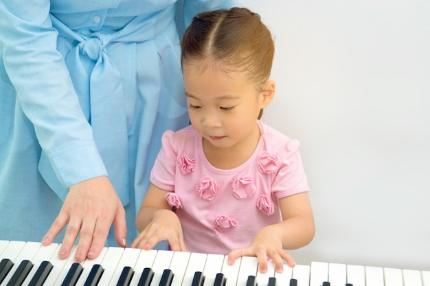Ta mère enseigne une petite fille au piano.