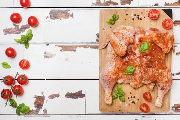 Tabac de poulet cru sur une planche de bois avec des épices et des légumes espace de copie