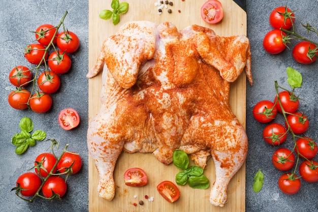 Tabac de poulet cru sur une planche de bois avec des épices et des légumes.
