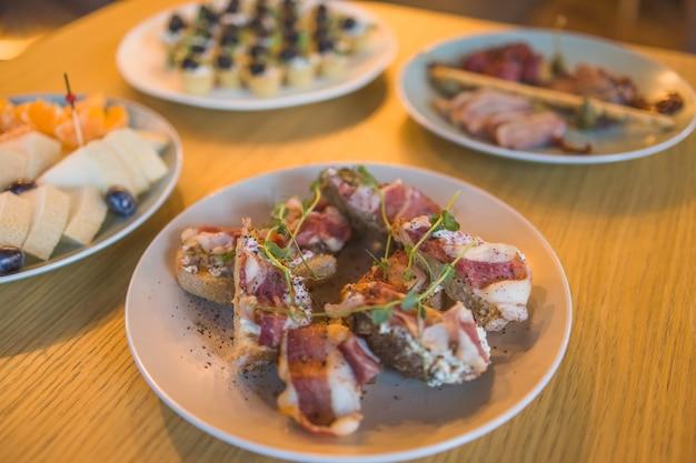 Table d'accueil buffet avec burgers, snacks froids, viandes et salades.