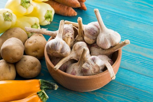 Sur la table, l'ail dans un bol et à côté des légumes
