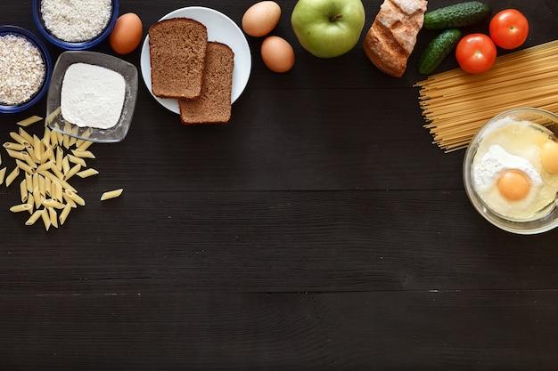 Table des aliments sains italien, légumes spaghetti sur un bureau en bois noir, vue de dessus