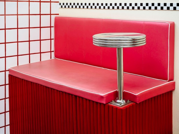 Table d'appoint ronde vide en acier inoxydable se fixant sur des cabines de style rétro rouge. mini support de boisson rond sur une banquette de bar vintage en cuir rouge vide près d'un fond de mur de carreaux blancs.