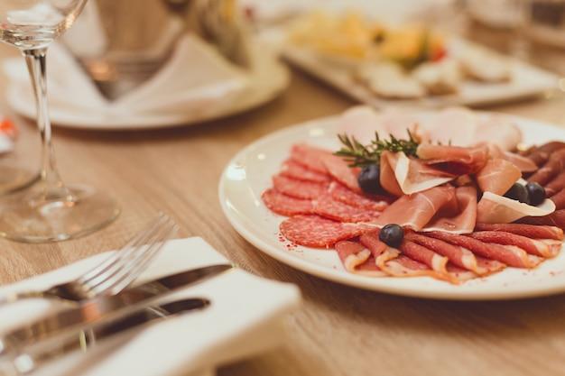 Table au restaurant avec collations à base de viande, couverts, verres à vin.