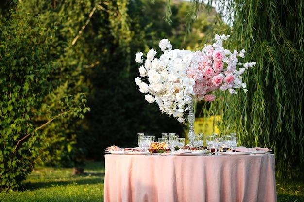 Table de banquet décorée en plein air avec des bougies et des fleurs séchées