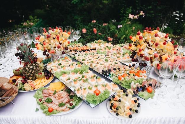 Table de banquet joliment décorée avec des salades, des bonbons, des fruits et des collations froides. une variété de délicieuses collations savoureuses sur la table. mise au point sélective