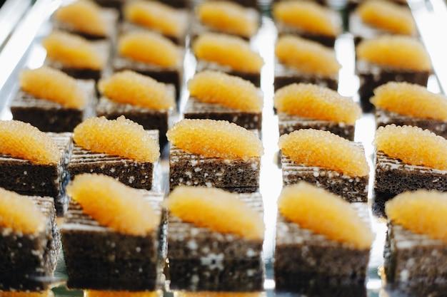 Table de banquet de restauration joliment décorée avec différentes collations et amuse-gueules avec sandwich, caviar, fruits frais lors d'une fête d'anniversaire de noël ou d'une célébration de mariage.