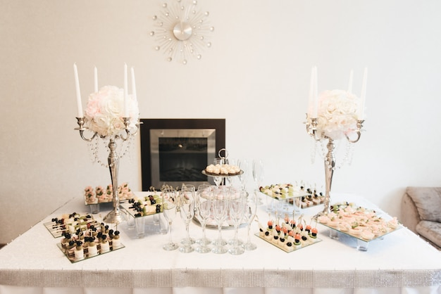 Table de banquet de restauration joliment décorée avec des hamburgers, des profiteroles, des salades et des collations froides. variété de délicieuses collations délicieuses sur la table