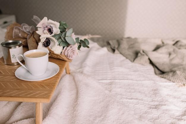 Table basse en bois avec des fleurs sur le lit avec plaid, tasse à café, fleurs et bougies. roses lilas à l'eucalyptus et aux anémones. tons gris intérieurs.