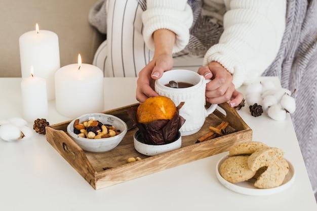 Sur la table basse sont des cartes, un livre, une tasse de thé chaud, des bougies. composition en gros plan.