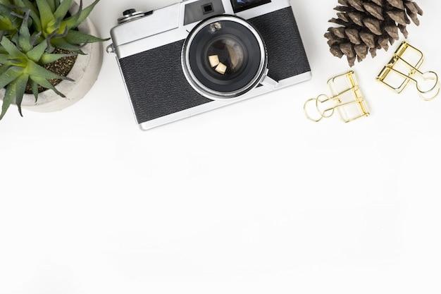 Table blanche avec appareil photo argentique et objets décoratifs.
