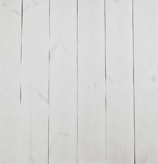 La table blanche en bois vide. le fond de planches peintes en bois