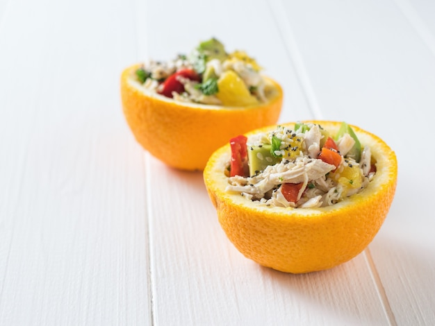 Table blanche avec deux moitiés d'orange remplies de salade