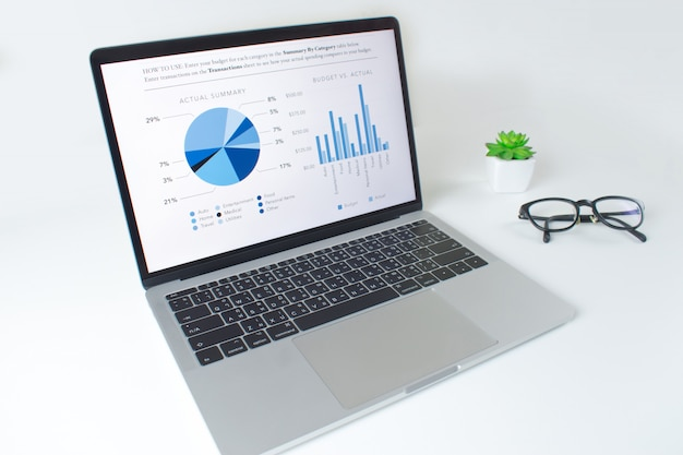 Table blanche moderne avec ordinateur portable avec rapport de statistiques financières