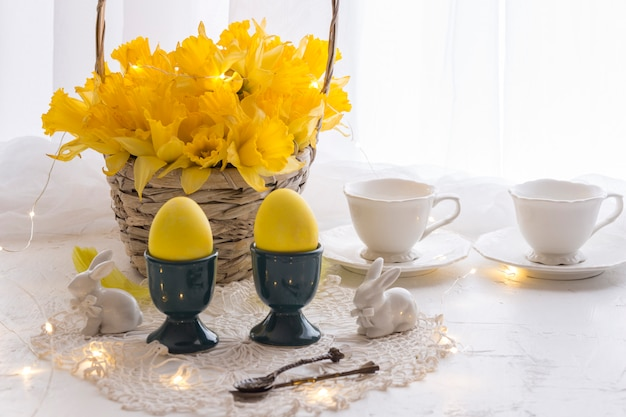 Sur une table blanche des oeufs jaunes, des jonquilles dans un panier, deux tasses et des figurines en forme de lapins