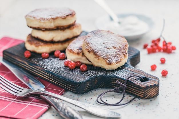 Sur une table blanche en pierre artificielle se trouve une planche à découper en bois avec cinq crêpes au fromage cottage et des fruits rouges. sur la table, une serviette à carreaux rouge, de la crème sure, une fourchette et un couteau.