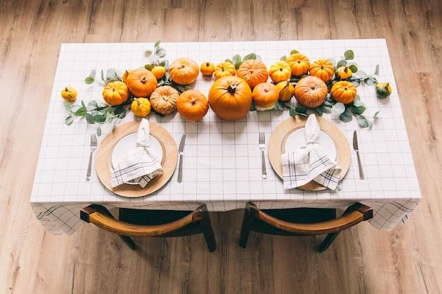 Table blanche avec des plats et de la nourriture dans la chambre. citrouilles jaunes sur la table à café.