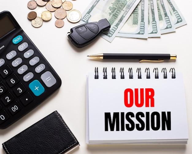 Sur une table blanche se trouve une calculatrice, une clé de voiture, de l'argent, un stylo et un cahier avec l'inscription notre mission