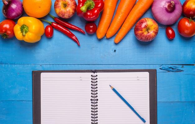 Table bleu avec des légumes et un bloc-notes