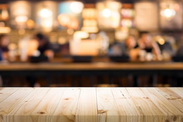 Table en bois avec arrière-plan flou de café.