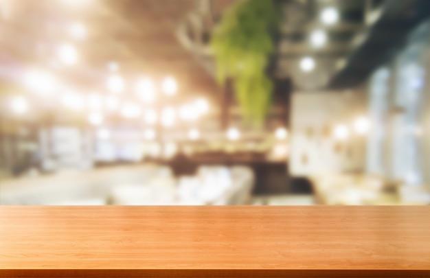 Table en bois en arrière-plan flou de salle de restaurant moderne ou café pour l'affichage des produits