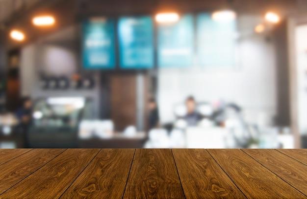 Table en bois en arrière-plan flou de salle de restaurant moderne ou café pour maquette d'affichage de produit.