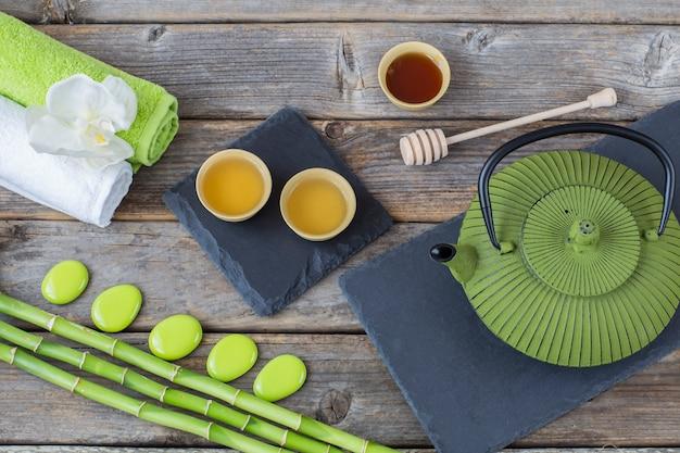 Sur une table en bois, bambou, serviettes, orchidée, thé dans des bols à boire, miel et théière - fond sur le spa