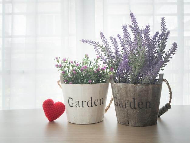 Table en bois avec belle fleur et signe de forme de coeur rouge sur fenêtre rideau blanc backgrou