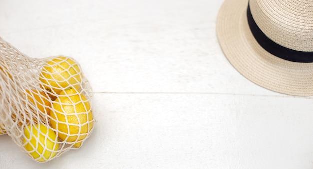 Sur une table en bois blanc, à côté se trouve un sac tricoté avec des citrons et un chapeau de paille.