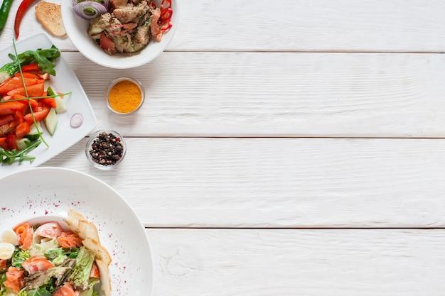 Table en bois blanc avec espace libre de salades chaudes. vue de dessus sur le bureau de la cuisine avec des plats d'accompagnement de viande, plat