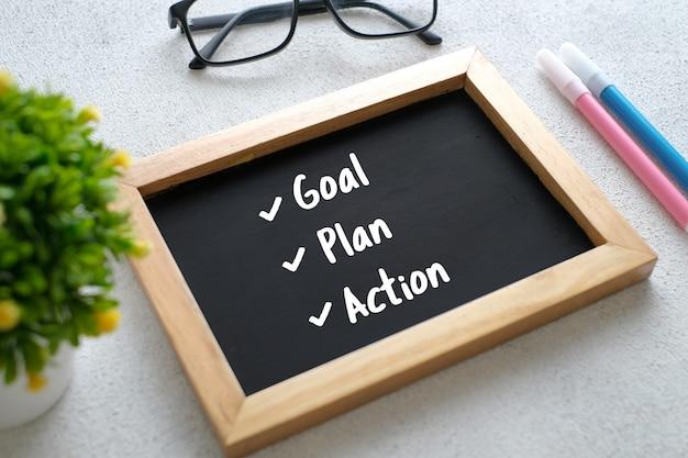 Table en bois blanc avec lunettes, stylo, plantes décoratives et tableau écrit avec l'action du plan objectifs 2021. vue de dessus avec espace de copie, mise à plat.
