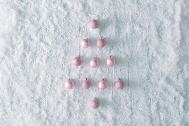 Table en bois blanc avec neige et sapin de noël avec décoration rose. vue de dessus d'hiver créative. mise à plat minimale avec espace de copie.