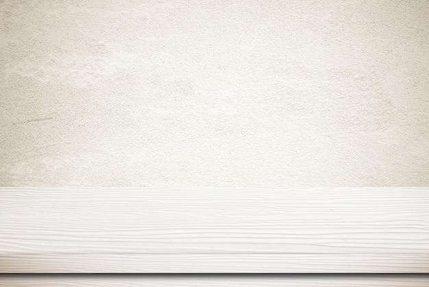 Table en bois blanc vide sur fond de mur de ciment grunge