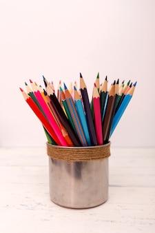 Table en bois blanche avec des crayons de couleur.