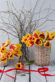 Sur une table en bois blanche tulipes dans un panier et des branches de bouleau dans un vase