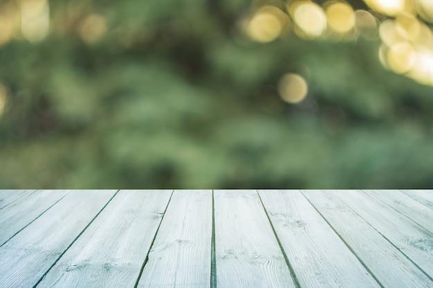 Table en bois bleue vide avec parc de la ville floue sur le fond. concept fête, produits, fond de printemps