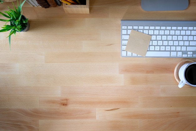 Table en bois de bureau avec ordinateur à clavier, tasse de café et fleur. vue de dessus avec espace de copie
