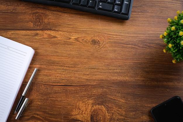 Table en bois avec cahier, loupe, stylo, plantes décoratives. vue de dessus avec espace de copie, mise à plat.