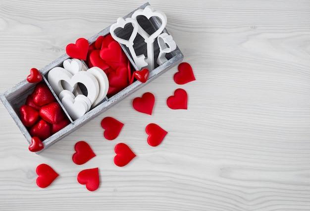 Sur une table en bois clair une boîte avec des coeurs, des bonbons et un décor