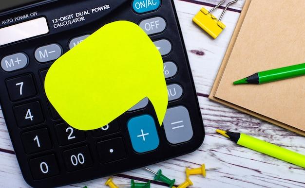 Sur une table en bois clair, il y a une calculatrice, un cahier, des crayons jaunes et verts, un clip jaune, des boutons et une carte jaune avec un emplacement pour insérer le texte. concept d'entreprise.