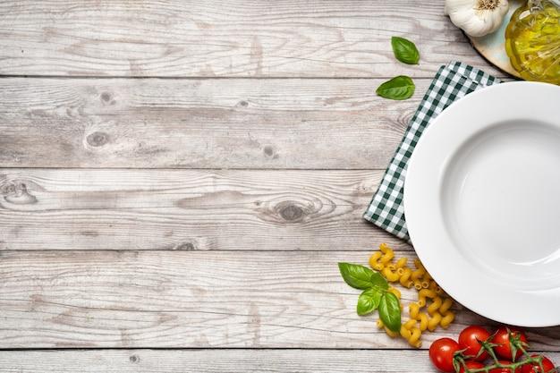 Table en bois de cuisson des aliments avec légumes, pâtes et assiette blanche vide.