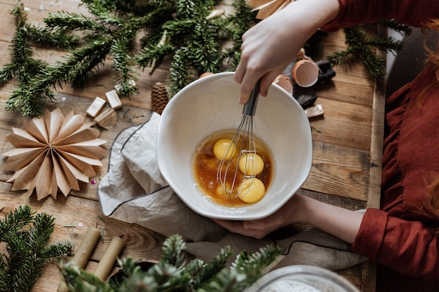 Sur une table en bois dans un bol blanc, battre les œufs avec le sucre.