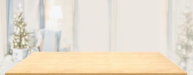 Table en bois avec décor de noël dans le salon flou avec lumière bokeh. affichage du produit de la publicité, maison de luxe.