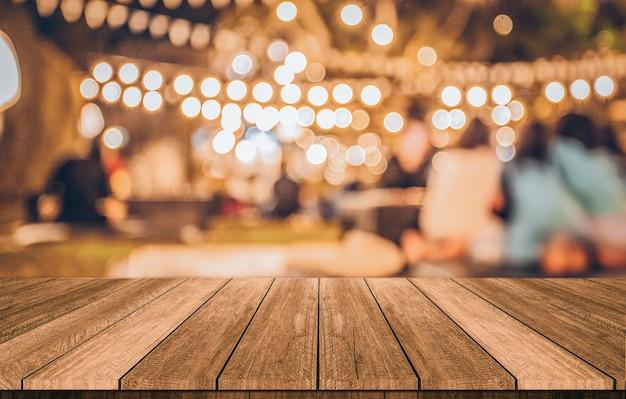 Table en bois devant le restaurant floue abstrait lumières