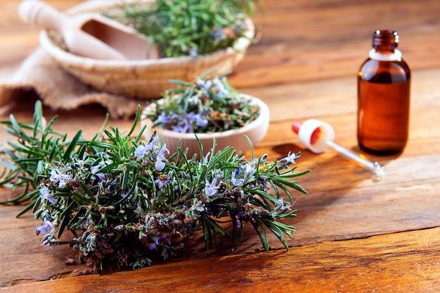 Table en bois avec du romarin vert et une préparation d'huile essentielle