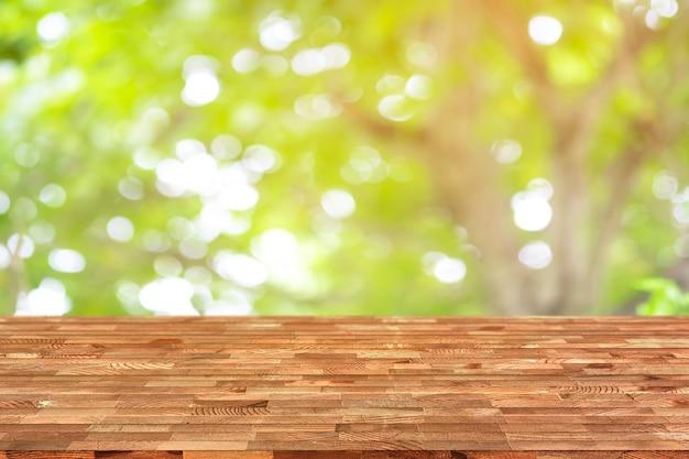 La table en bois emtry sur le dessus du fond naturel flou, peut être utilisé en maquette.
