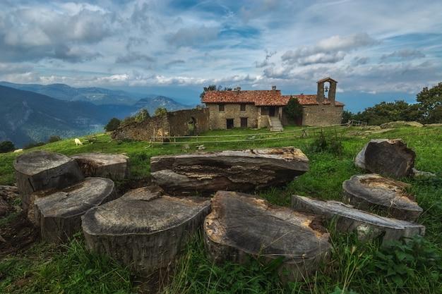 Une table en bois entourée de sièges en bois avec une vieille maison avec un clocher et des montagnes lointaines en catalogne, espagne