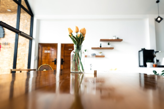 Table en bois et fleurs dans un arrière-plan flou de café