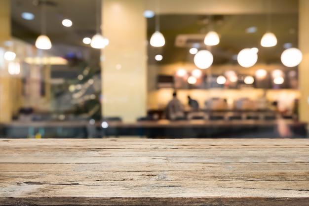 Table en bois sur fond de café café de flou.