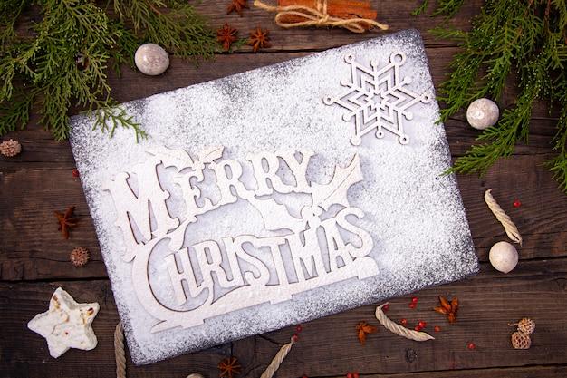 Table en bois, friandises de fête, pain d'épices, épices, branches d'arbres de noël, plateau en pierre d'une bonne année.